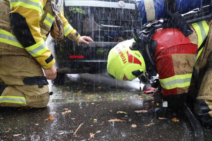 Polizist und Feuerwehr löschen Fahrzeugbrand