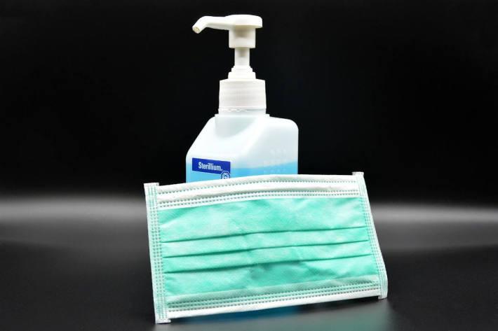 Symbolbild – Atemschutzmaske und Desinfektionsmittel