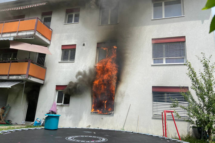 Flammen schlagen aus einem Fenster der brennenden Wohnung