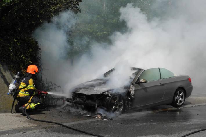 Löscharbeiten am in Brand geratenem Fahrzeug