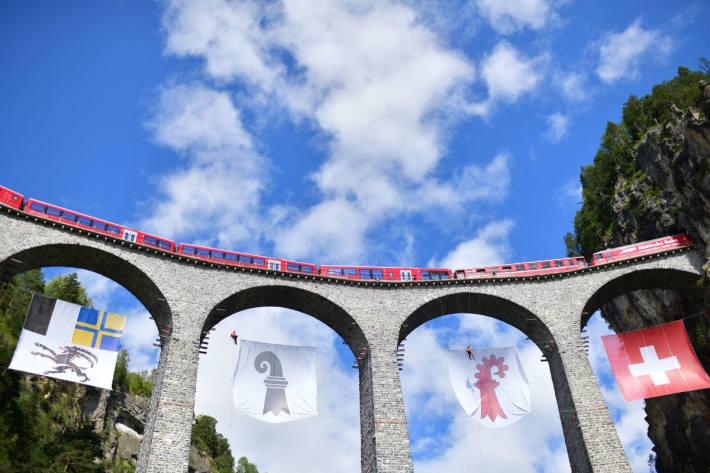 Flaggen aller drei Kantone am Wahrzeichen Graubündens, dem Landwasserviadukt.