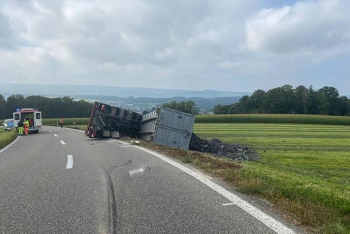 Mit Schrott beladener Lastwagen umgekippt