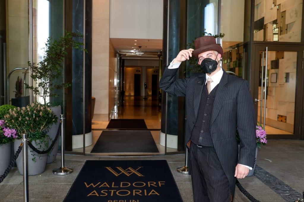 Ein Portier im Waldorf Astoria Berlin bereitet sich darauf vor, Freizeitgäste zu begrüßen, während die Hotels in der Hauptstadt wieder für Touristen öffnen. Die Suchanfragen für die Hilton Hotels in Berlin sind im Vergleich zum Vormonat um 48 Prozent gestiegen, da Reisende wieder Wochenendtrips in die Stadt buchen möchten. Im Laufe des nächsten Monats wird das Team des Luxushotels im Stadtzentrum rund 5.000 Handtücher waschen, 2.100 Frühstücke servieren, 2.000 Bademäntel bügeln und sich darauf vorbereiten, 150 Champagnerkorken knallen zu lassen, wenn die Urlaubszeit wieder beginnt. / Weiterer Text über ots und www.presseportal.de/nr/131988 / Die Verwendung dieses Bildes ist für redaktionelle Zwecke unter Beachtung ggf. genannter Nutzungsbedingungen honorarfrei. Veröffentlichung bitte mit Bildrechte-Hinweis.