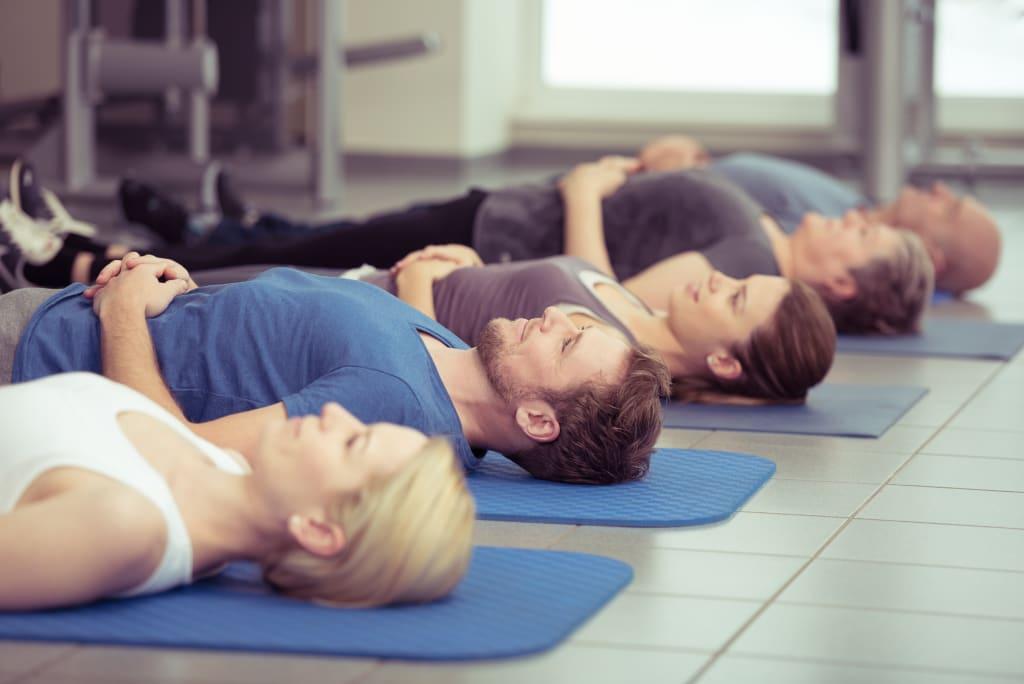 Männer und Frauen praktizieren Entspannungsübungen. (Foto: pro psychotherapie e.V./contrastwerkstatt)