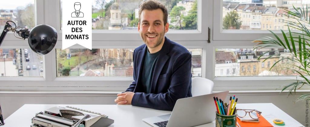 Der Autor James Bailey sitzt an seinem Schreibtisch