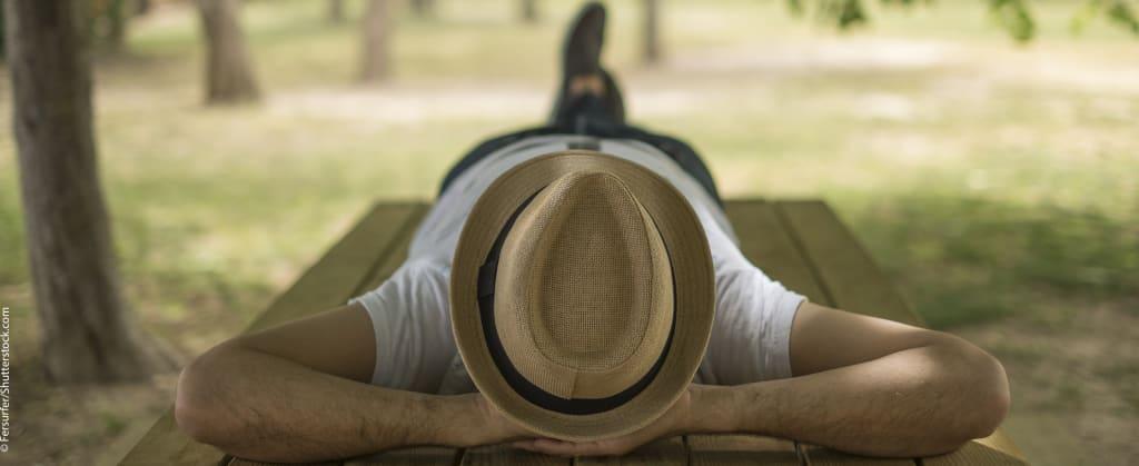Ein Mann liegt auf einem Tisch im Park auf dem Rücken, mit dem Kopf zum Betrachter und hat einen Hut auf
