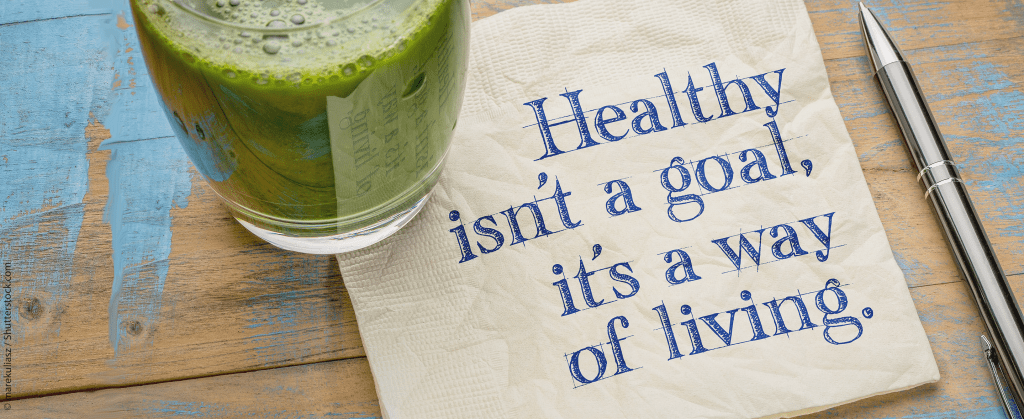"""Glas mit grünem Smoothie steht auf einer Serviette mit der Aufschrift """"Healthy isn't a goal, it's a way of living."""""""