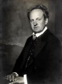 Porträt des Schriftstellers und Dramatikers Gerhart Hauptmann in formalem Anzug vor dunklem Hintergrund