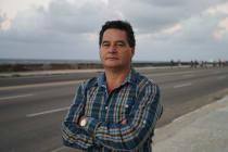Der kubanische Autor Ángel Santiesteban steht in gestreiftem Hemd mit verschränkten Armen vor einer Landstraße, im Hintergrund flaches Land und ein bewölkter Himmel