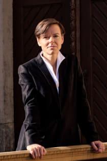 Die Autorin Antje Rávik Strubel blickt in die Kamera. Sie trägt das kurze Haar in einem Seitenscheitel, unter dem schwarzen Jacket eine weiße Bluse mit stehendem Kragen.