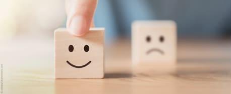 Zwei Bauklötze aus Holz, einer mit lächelndem, der andere mit traurigem Gesicht. Der mit dem lächelnden Gesicht wird von einem Menschen nach vorne geschoben, der traurige verschwimmt leicht im Hintergrund.