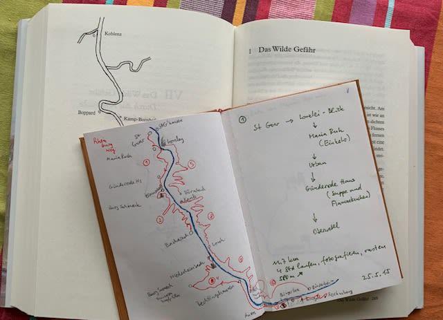 Eine Aufnahme von einem aufgeschlagenen Notizbuch. Über beide Seiten ist eine handgemalte Karte eines Flussverlaufs mit Notizen. Das Notizbuch liegt auf einem Buch, in dem eine ähnliche Karte abgedruckt ist.