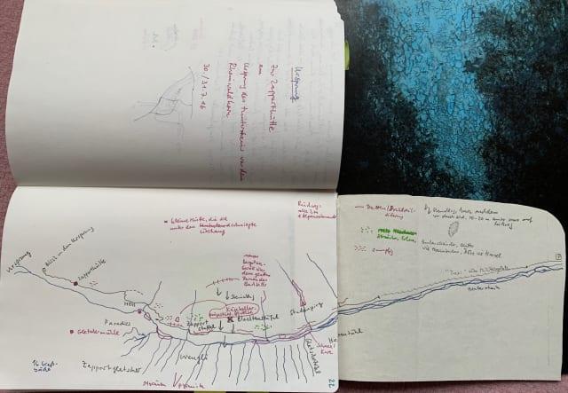 Ein aufgeschlagenes Notizbuch, aus dem eine eingeklebte Seite zusätzlich herausgeklappt ist. Über alle drei Seiten eine handgefertigte Zeichnung eines Flussverlaufs mit Notizen