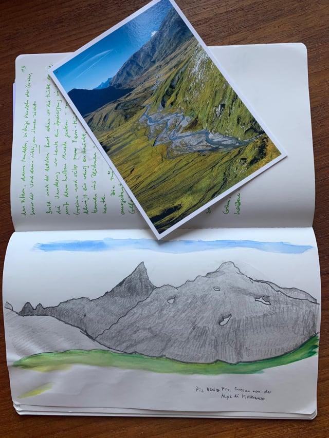 Ein aufgeschlagenes Notizbuch. Auf einer Seite eine Zeichnung einer Bergkette und des davorliegenden Tals, auf der anderen Seite handschriftliche Notizen. Auf den Notizen liegt eine Postkarte mit einer Ansicht des Greina-Tals