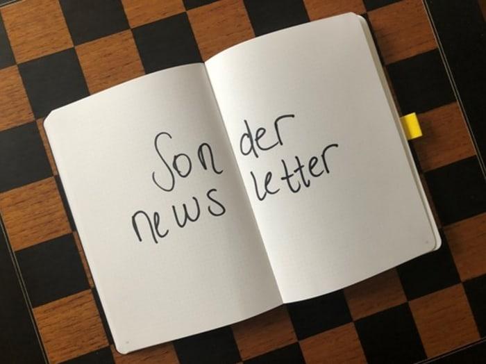 Foto von einem Schachfeld, auf dem ein aufgeschlagenes Notizbuch liegt. Über zwei Seiten steht geschrieben: Sondernewsletter