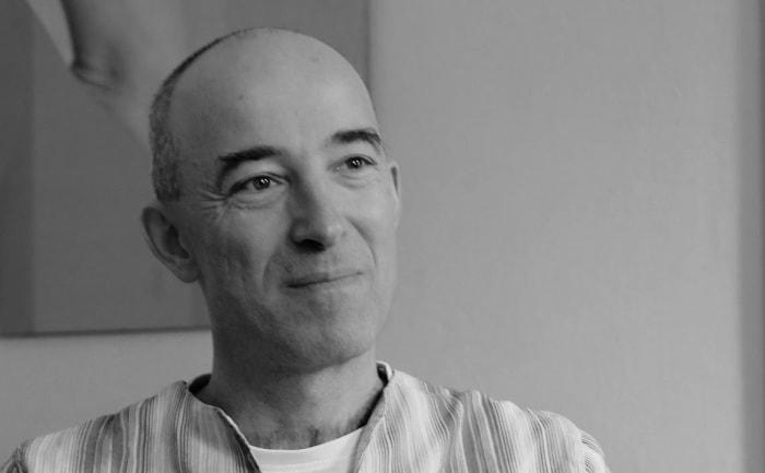 Übersetzer Luis Ruby in Hemd und weißem T-Shirt vor einem Gemälde