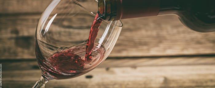 brauner Holzboden, darüber ein gehaltenes Glas Wein, in das Rotwein gegossen wird