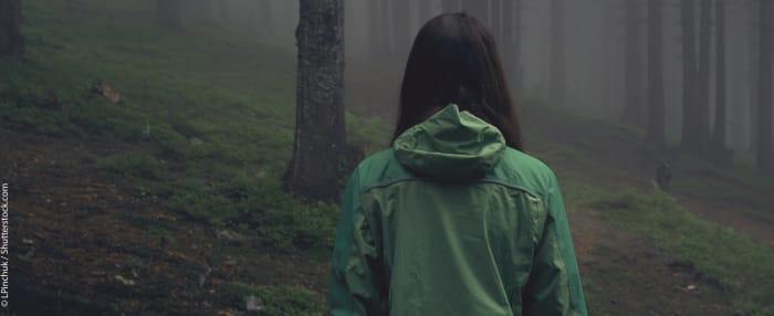 Frau von hinten in einem nebelverhangenen Wald in anfangender Dunkelheit