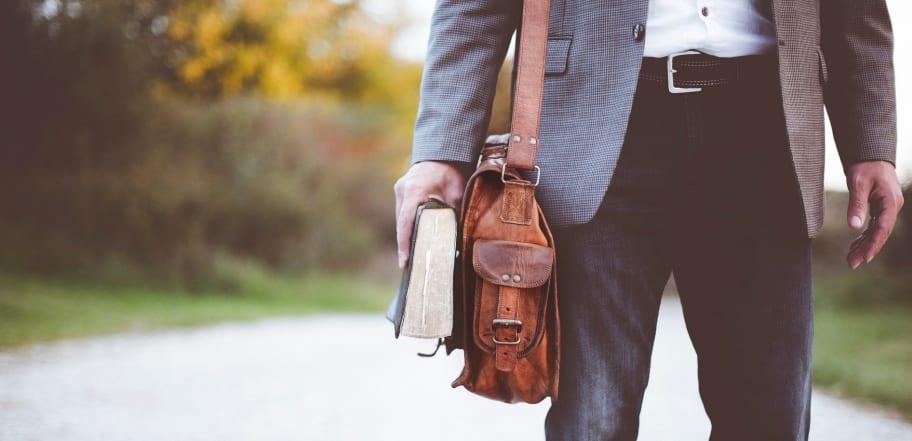 Mann auf dem Weg zur Arbeit mit Buch