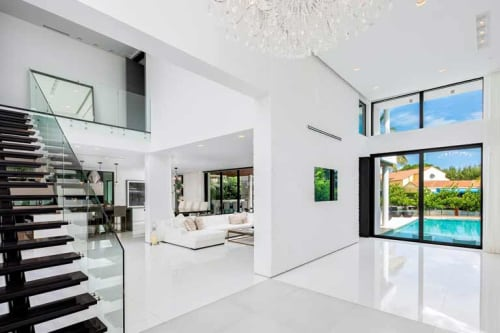 Interior of a modern home with marble floors, glass staircase, chandelier, and pool outside a floor-to-ceiling window visible