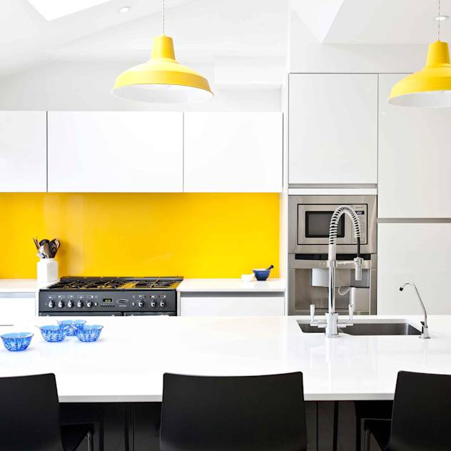 White, black, stainless steel and a vibrant splash of yellow. : Cucina moderna di Pyram