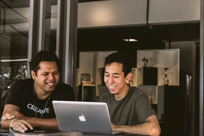 Two small business owners sit at a table looking at a laptop while smiling