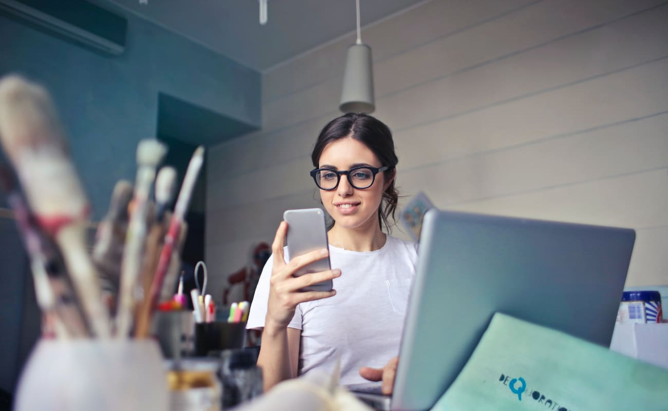 Small business owner on laptop and looking at smartphone to track time