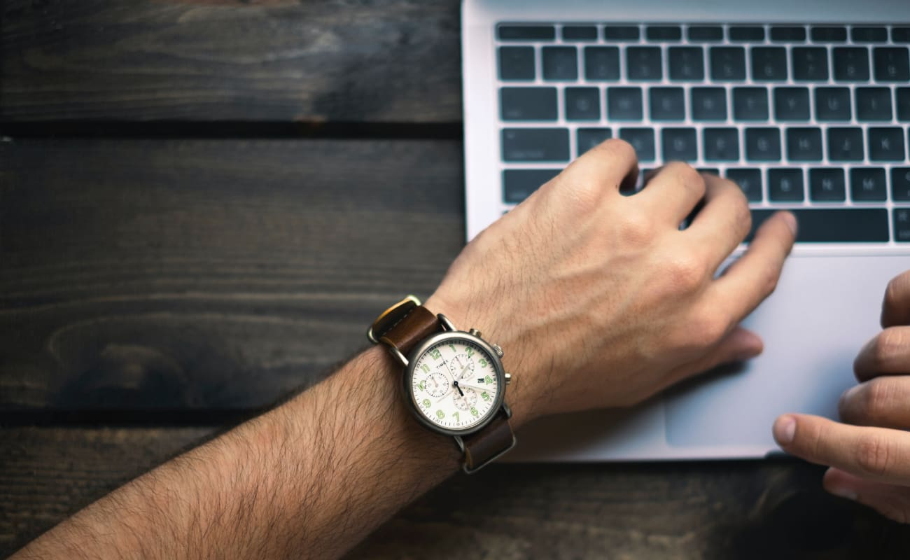 Man's hand on laptop keys showing watch for time tracking