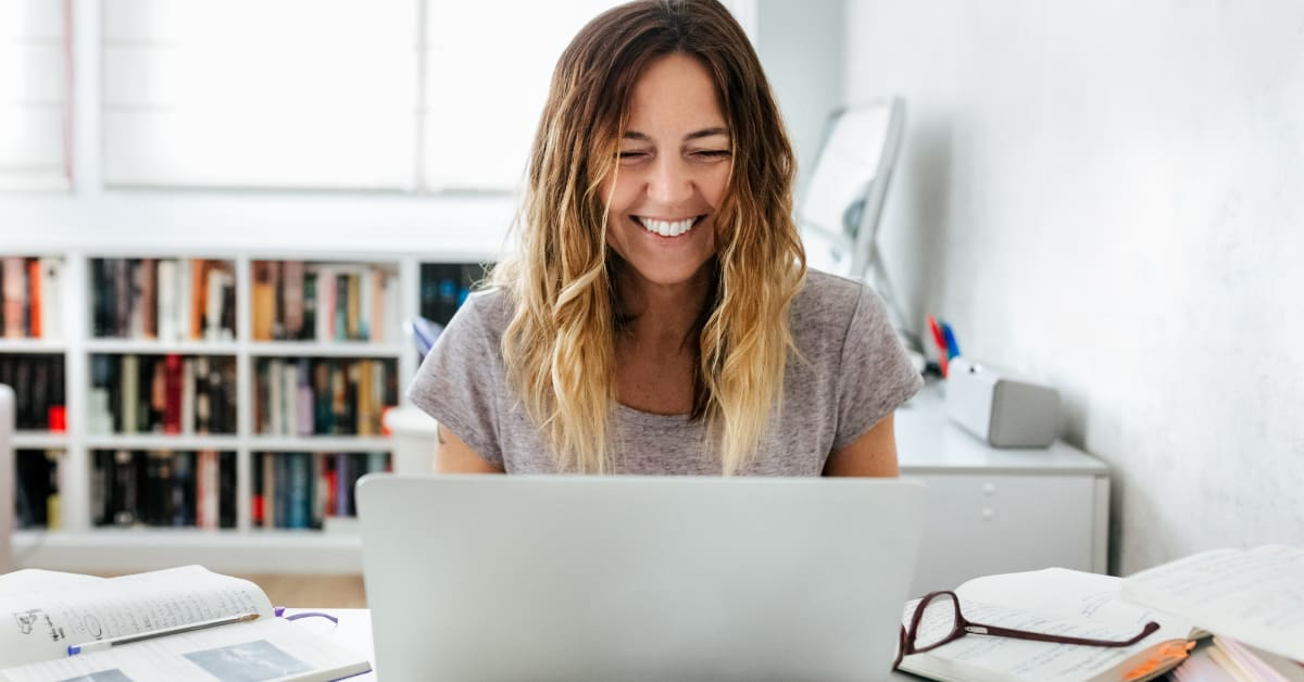 Woman sitting at a table looking down at a laptop and smiling