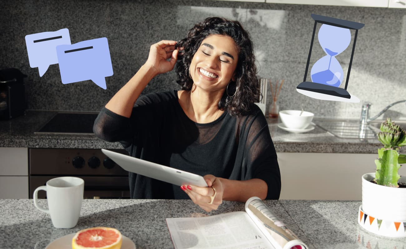 Woman sits in kitchen smiling down at an ipad. There's a speech bubble and hourglass illustration next to her.