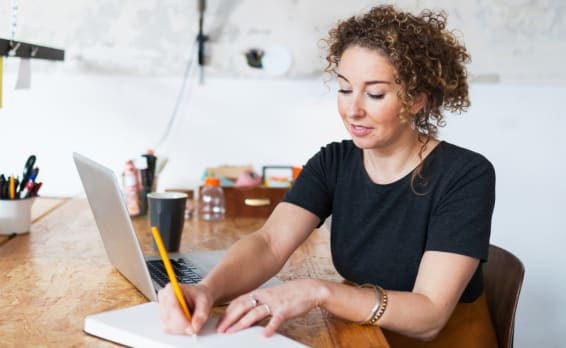 Woman sits at desk with laptop open but she's looking down at a journal and writing with a pencil