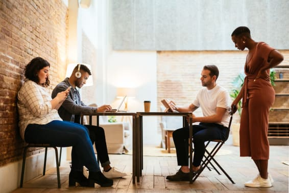 Diverse Coworkers Using Devices In Office