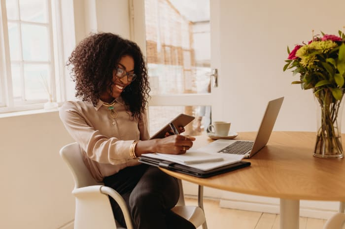 Black women sits at desk smiling and looking at her phone. There is a computer and note book on the desk in front of her.