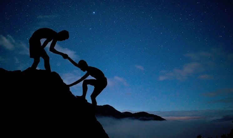 A night sky with a person helping another climb a rock.