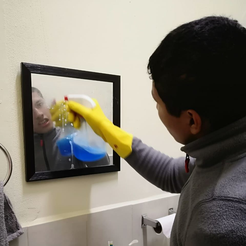 Diego cleaning a bathroom mirror