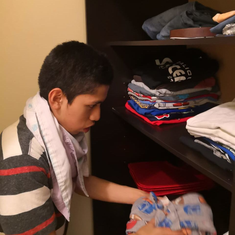 Carlos putting away clothes