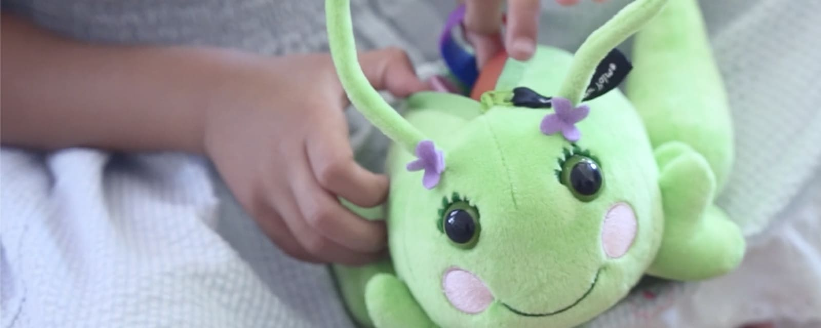 Smiling Poppie grasshopper plush with purple flowers and zipper pocket.