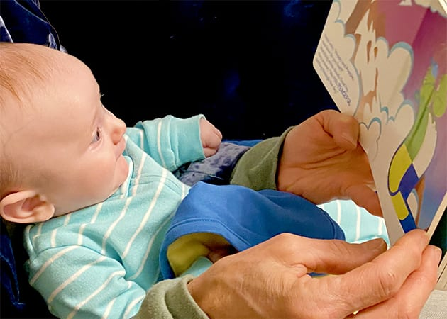 Baby and grandmother reading What We Feel board book