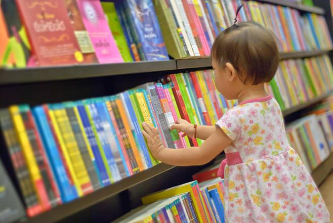 little girl choosing books reading to babies