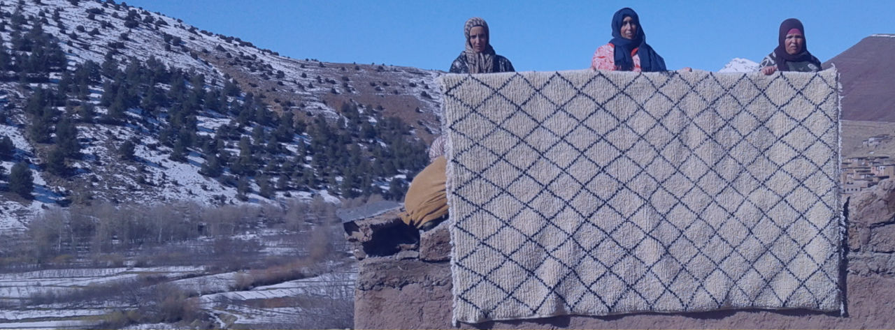 photograph of artisan with rug