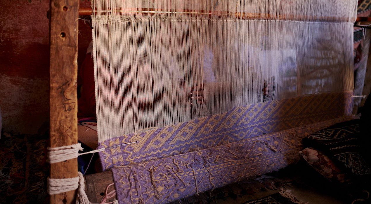 photograph of artisan with rug