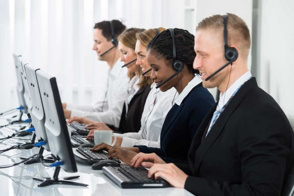 Five people using a call centre dialler on computers and headsets