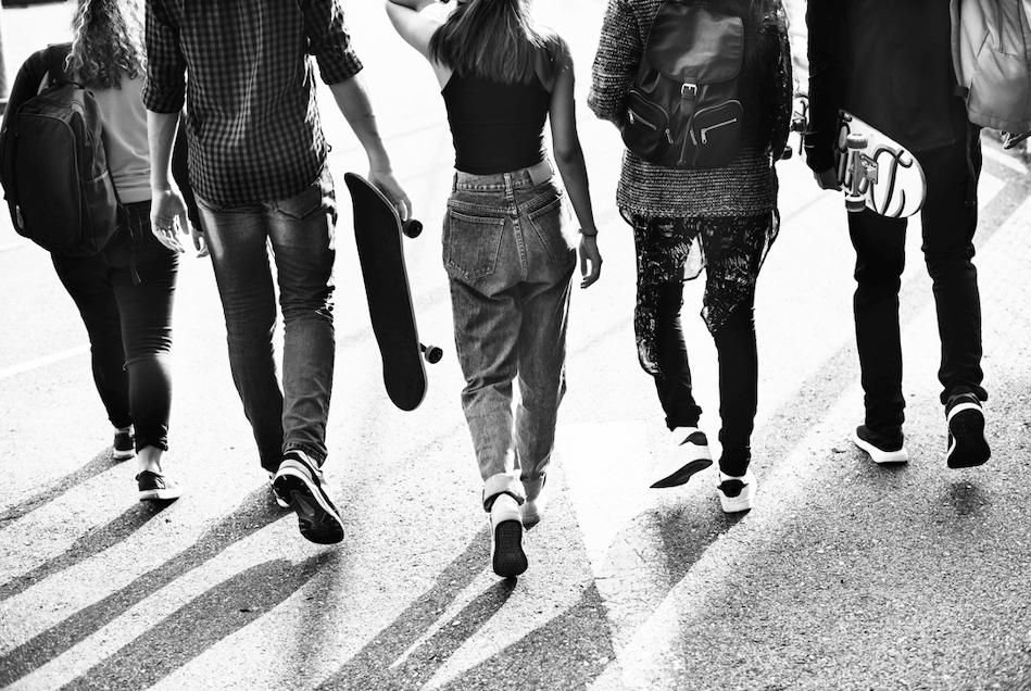 Black and white photo of group of teenagers walking with skateboards.