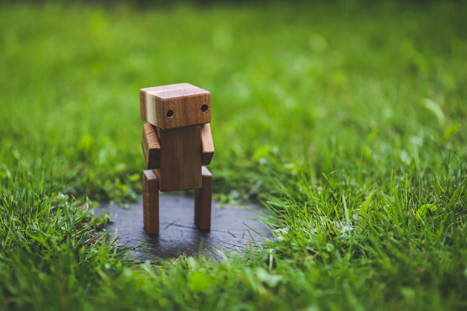 A wooden robot in the grass