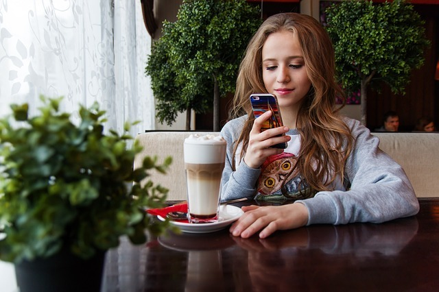 A teen on her phone in a café.