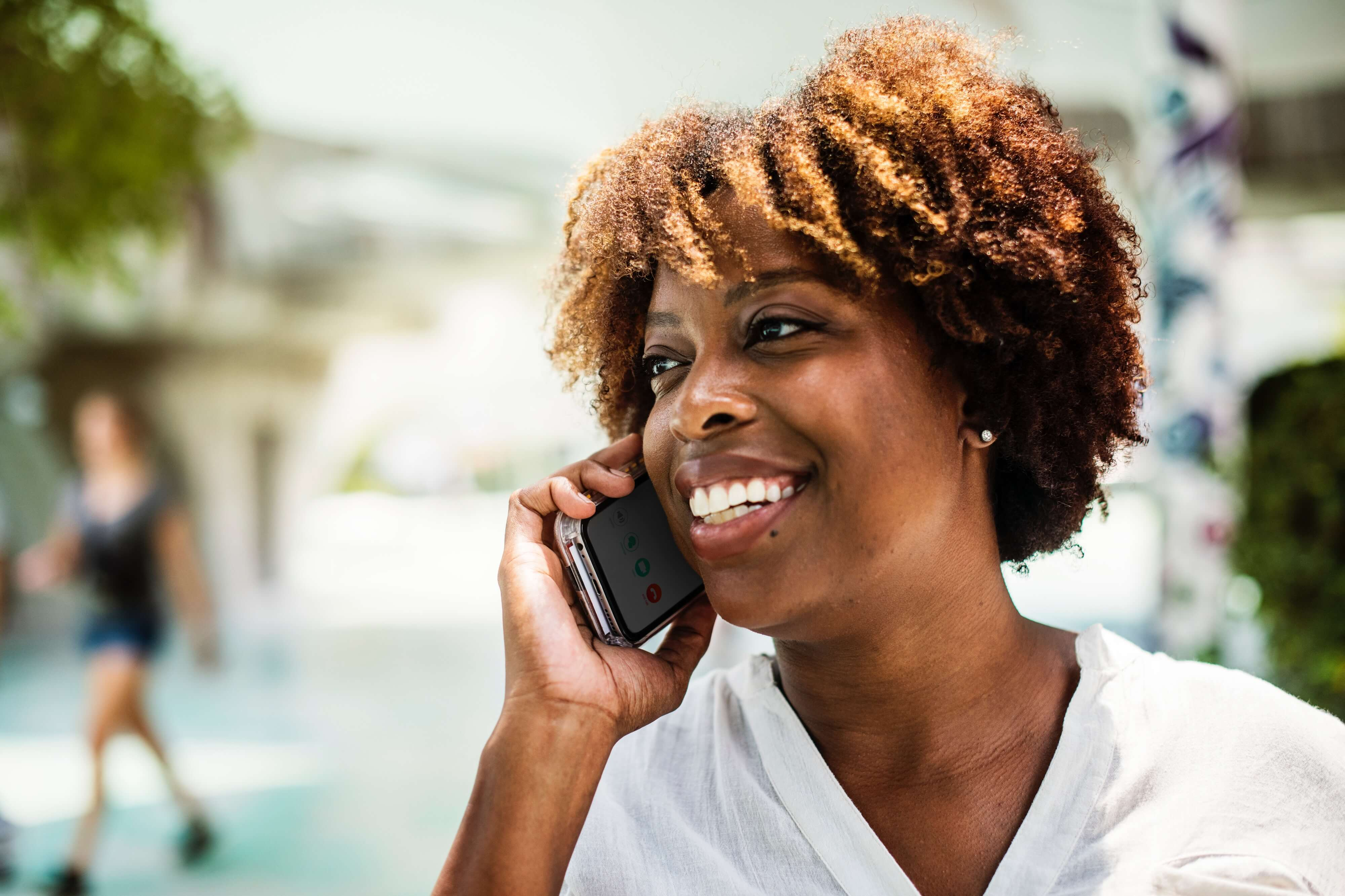 A woman on the phone, smiling.
