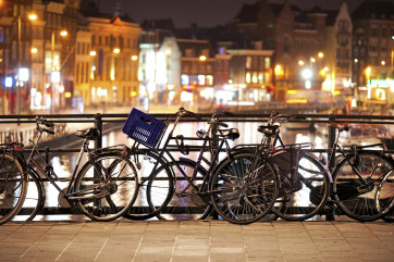 Amsterdam's famous bicycles by the canal at night