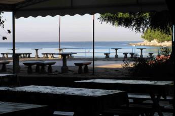 Pula : hostal Pula patio con bancos y mesas picnic