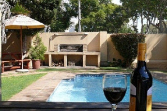 Cape Town - A Sunflower Stop : A glass of wine by the outdoor swimming pool at Cape Town A Sunflower Stop