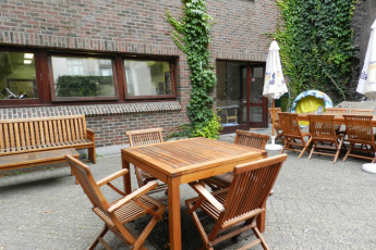 Brussels - Bruegel : Patio with tables and chairs at the hostel